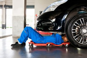 Mechanic,In,Blue,Uniform,Lying,Down,And,Working,Under,Car